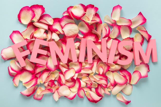 A palavra feminismo em cima de pétalas de rosa