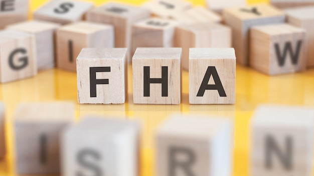 A palavra fha é escrita em uma estrutura de cubos de madeira. blocos em um fundo brilhante. conceito financeiro. foco seletivo. fha - abreviação de finance houses association