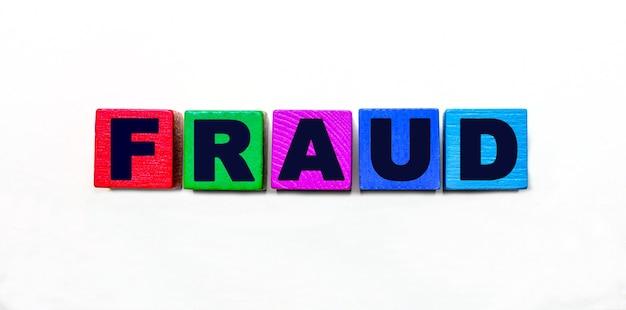A palavra fraude é escrita em cubos coloridos sobre um fundo claro
