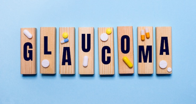 A palavra glaucoma está escrita em blocos de madeira em uma parede azul perto dos comprimidos. conceito médico