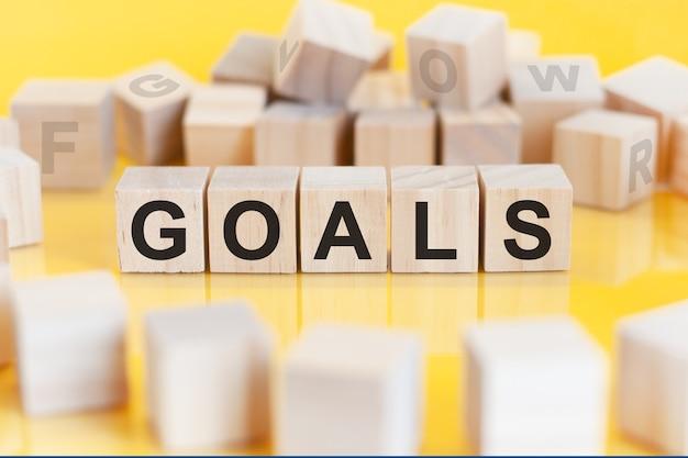 A palavra goals está escrita em uma estrutura de cubos de madeira. blocos em um fundo amarelo brilhante. pode ser usado para negócios, educação, conceito financeiro. foco seletivo.