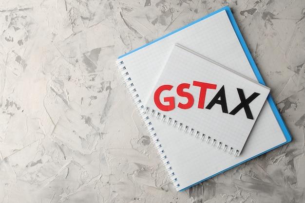 A palavra gst tax com um bloco de notas sobre um fundo claro e concreto. vista de cima com espaço para texto