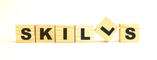 A palavra habilidades. cubos de madeira com letras isoladas no fundo branco. imagem conceitual.