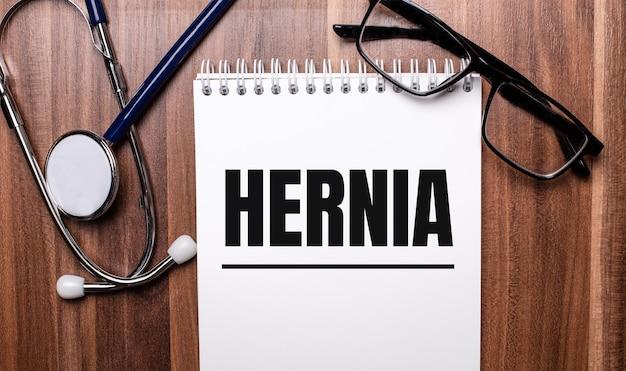 A palavra hérnia está escrita em papel branco em uma parede de madeira perto de um estetoscópio e óculos de armação preta. conceito médico