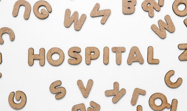 A palavra hospital entre muitas letras de madeira no fundo branco. vista superior