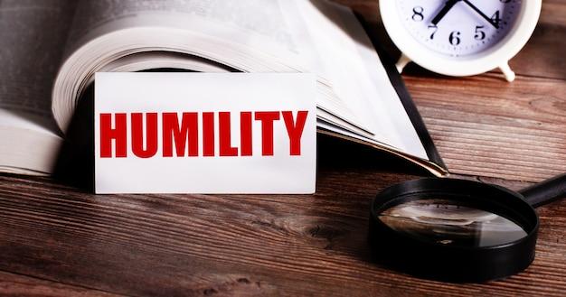 A palavra humildade escrita em um cartão branco perto de um livro aberto, despertador e lupa