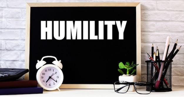A palavra humildade está escrita no quadro-negro ao lado do despertador branco, óculos, vasos de plantas e lápis em um suporte.
