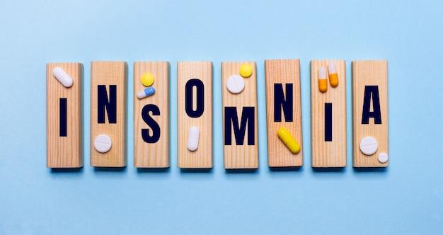 A palavra insônia está escrita em blocos de madeira em uma mesa azul clara perto dos comprimidos