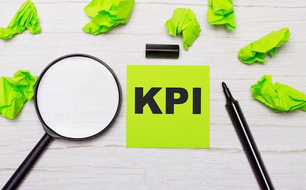 A palavra kpi escrita em uma nota adesiva verde ao lado de uma lupa e um marcador preto em uma mesa de madeira