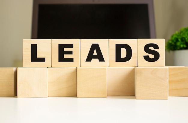 A palavra leads é escrita em cubos de madeira na mesa do escritório na frente de um laptop.