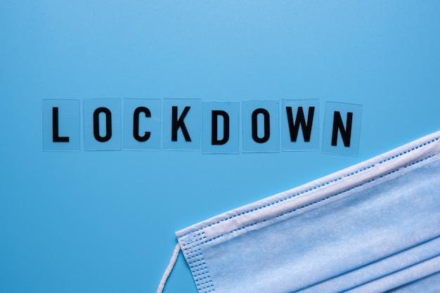 A palavra lockdown e uma máscara médica sobre um fundo azul. segunda onda covid 19.