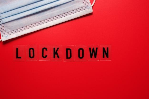 A palavra lockdown e uma máscara médica sobre um fundo vermelho. segunda onda covid 19.