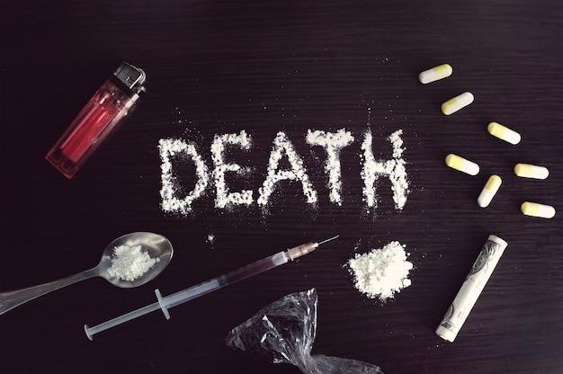 A palavra morte escrita em cocaína em uma mesa preta cercada por várias drogas pesadas. o conceito de vício.