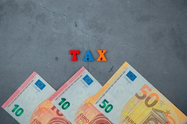 A palavra multicolorida de impostos é feita de letras de madeira em um fundo de parede gessada cinza.