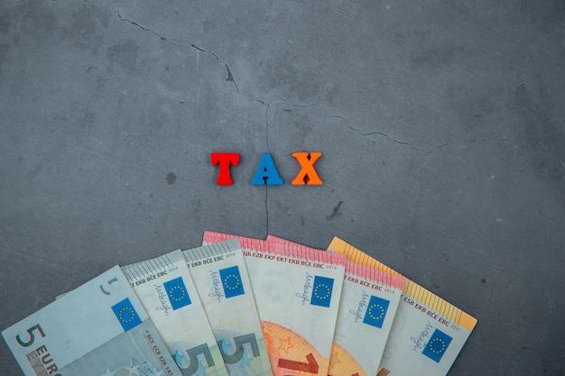A palavra multicolorida do imposto é feita de letras de madeira em uma parede emplastrada cinzenta.
