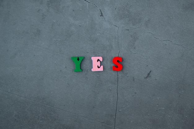 A palavra multicolorida do yes é feita de letras de madeira em uma parede emplastrada cinzenta.