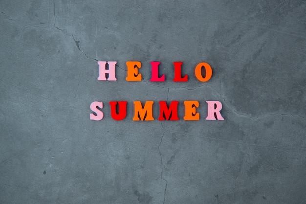 A palavra multicolorido olá verão é feita de letras de madeira em uma parede cinza rebocada.