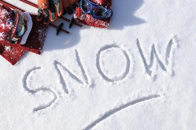 A palavra neve com roupas e equipamentos de esqui