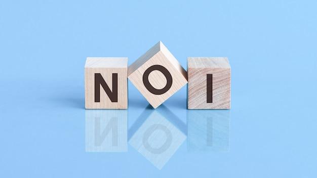 A palavra noi é feita de cubos de madeira sobre a mesa azul, conceito