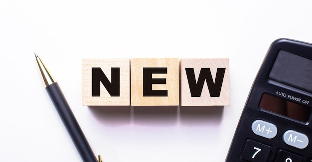 A palavra novo é escrita em cubos de madeira entre uma caneta e uma calculadora em uma superfície clara