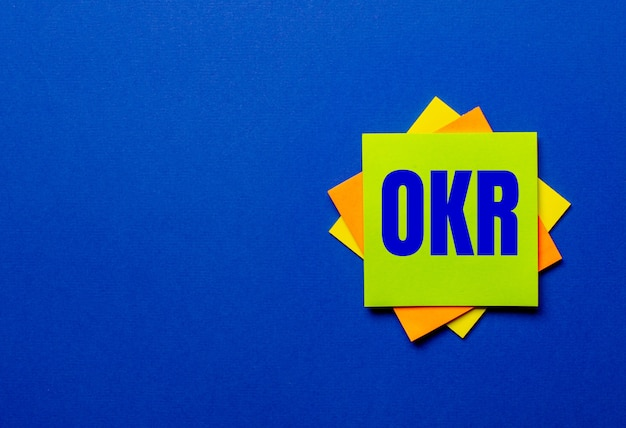 A palavra okr objective key results está escrita em adesivos brilhantes em um fundo azul