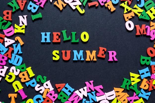 A palavra olá no verão de letras de madeira multi-coloridas em um fundo preto