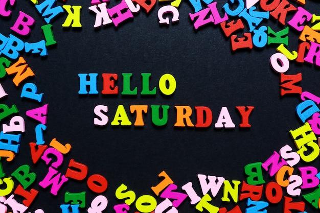 A palavra olá sábado de letras de madeira multi-coloridas em um fundo preto