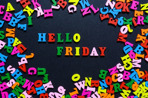 A palavra olá sexta-feira de letras de madeira multi-coloridas sobre um fundo preto