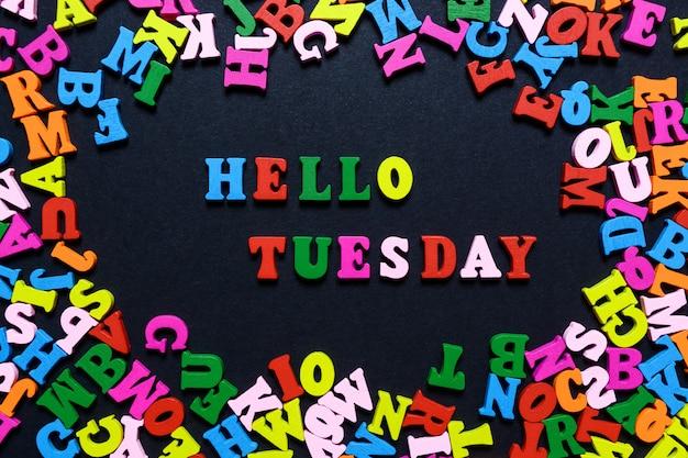 A palavra olá terça-feira de letras de madeira multi-coloridas em um fundo preto