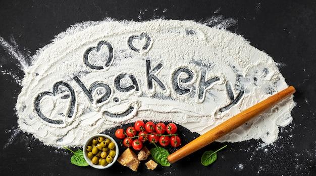 A palavra padaria e coração é escrita na farinha com rolo e ingredientes para fazer comida italiana, vista superior. fundo abstrato de cozimento