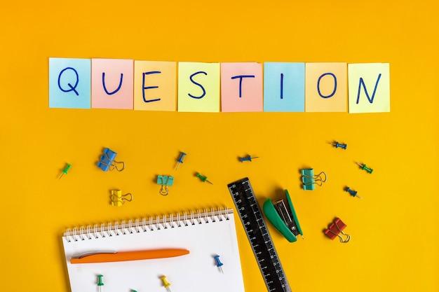 A palavra pergunta está escrita em adesivos coloridos em uma parede amarela com materiais de escritório