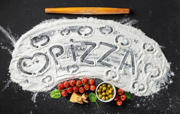 A palavra pizza e coração é escrita na farinha com rolo e ingredientes para fazer pizza italiana, vista superior. fundo abstrato de cozimento