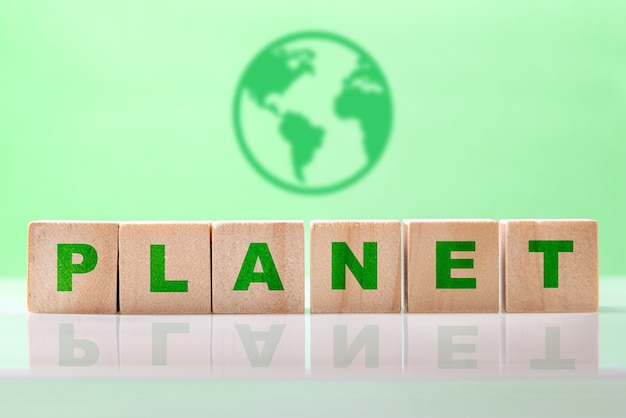 A palavra planeta escrita em cubos de madeira contra fundo verde claro com ícone de terra. salvar o conceito de ecologia do planeta terra