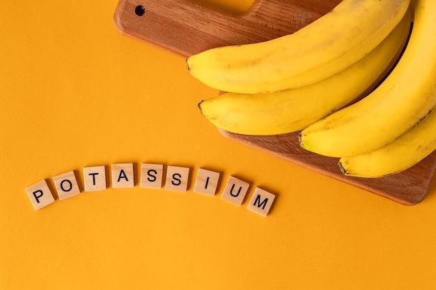 A palavra potássio é colocada em blocos de madeira no meio de bananas em um fundo amarelo