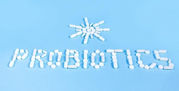 A palavra probióticos e o sol aparecem em comprimidos brancos sobre um fundo azul. o conceito de medicina, intestinos saudáveis