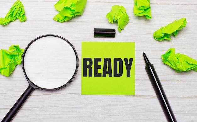 A palavra pronto escrita em uma nota adesiva verde ao lado de uma lupa e um marcador preto em uma mesa de madeira