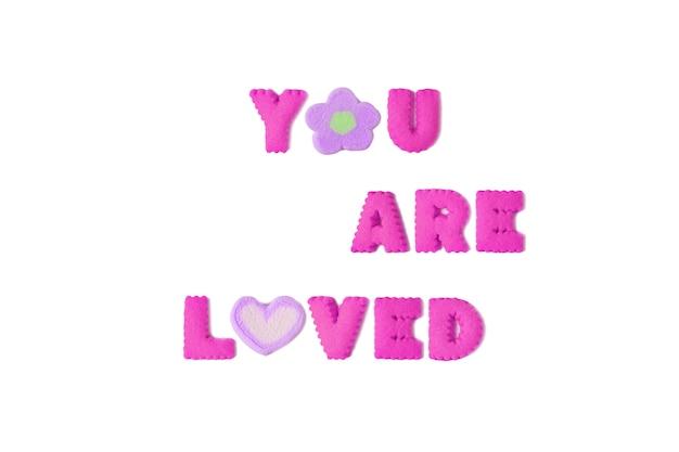 A palavra que você é amado soletrado com biscoitos alfabeto rosa e marshmallow