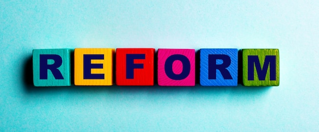 A palavra reformar está escrita em cubos de madeira brilhantes multicoloridos em uma mesa azul clara