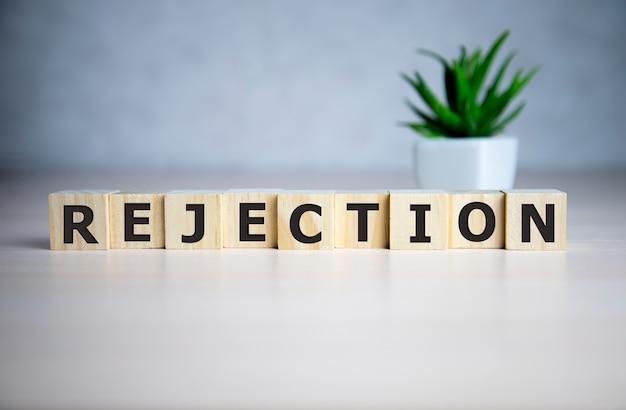 A palavra rejeição, escrita com ladrilhos de letras de madeira em azul