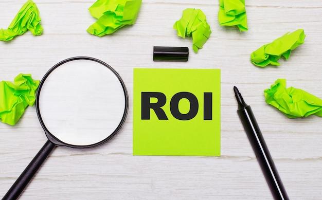 A palavra roi escrita em uma nota adesiva verde ao lado de uma lupa e um marcador preto em uma mesa de madeira