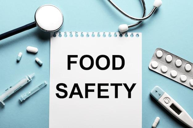 A palavra segurança alimentar escrita em um bloco de notas branco em uma superfície azul perto de um estetoscópio, seringa, termômetro eletrônico e comprimidos