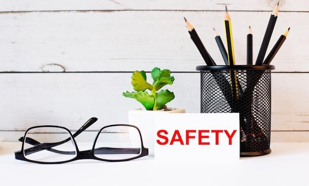 A palavra segurança escrita em um cartão de visita branco ao lado de lápis em um suporte e óculos. perto está um vaso de planta ...