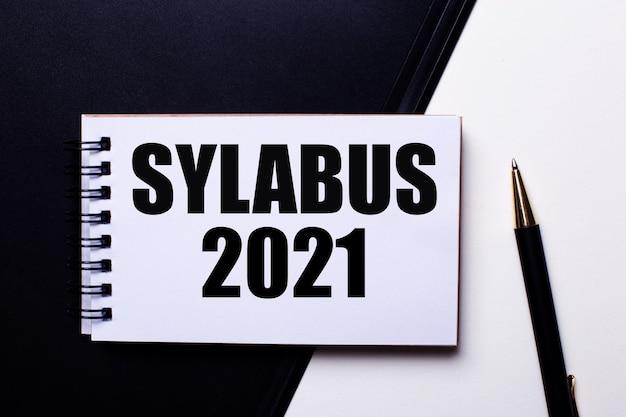 A palavra sylabus 2021 escrita em vermelho em uma mesa preta e branca perto da caneta