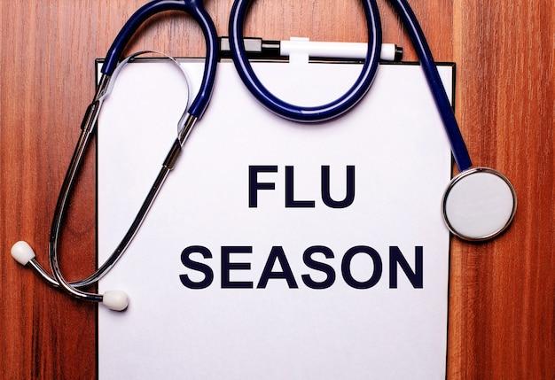 A palavra temporada da gripe está escrita em papel branco em uma parede de madeira perto de um estetoscópio e óculos de armação preta. conceito médico