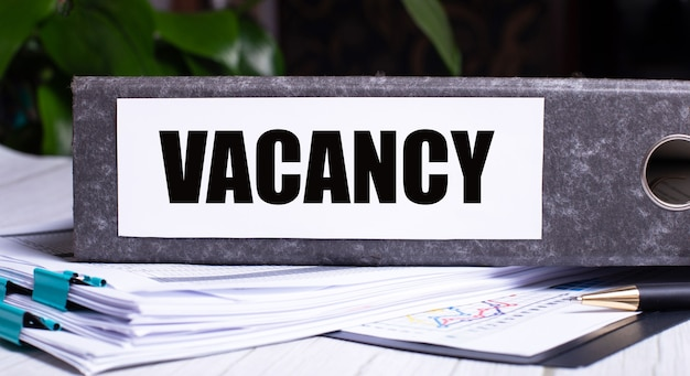 A palavra vacancy é escrita em uma pasta cinza ao lado dos documentos