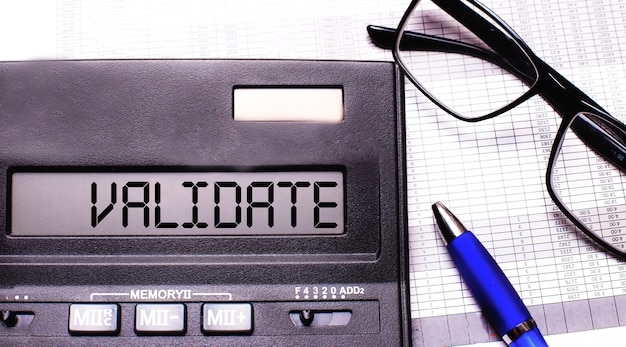A palavra validar está escrita na calculadora perto de óculos de armação preta e uma caneta azul