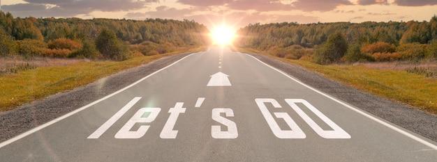 A palavra vamos escrita na estrada rodoviária no meio de uma estrada de asfalto vazia no lindo pôr do sol