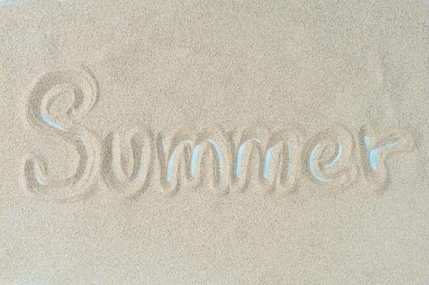 A palavra verão está escrevendo na areia. fundo de verão.