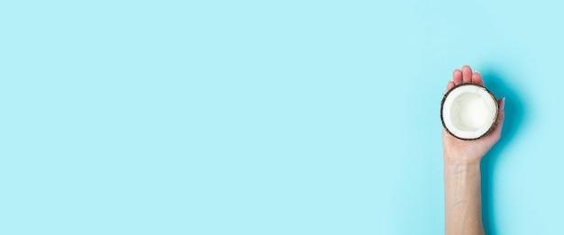 A palma da mão de uma mulher segura a metade aberta de um coco sobre um fundo azul. vista superior, configuração plana. bandeira.