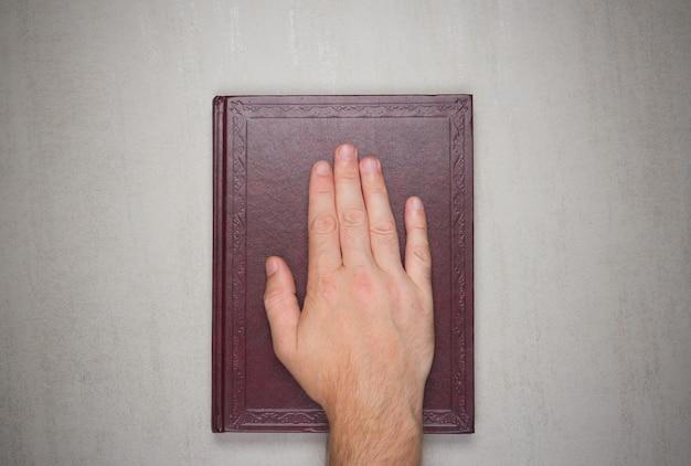 A palma de um homem em um livro, um juramento na bíblia.